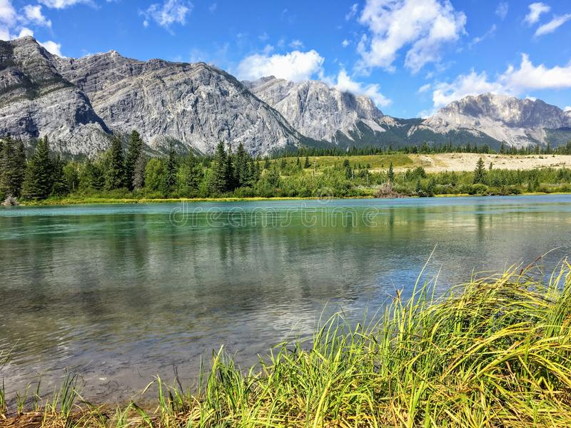 A view of the beautiful turquoise bow river flowing with the Rocky Mountains of kananaskis behind it and reflecting in the water. royalty free stock images