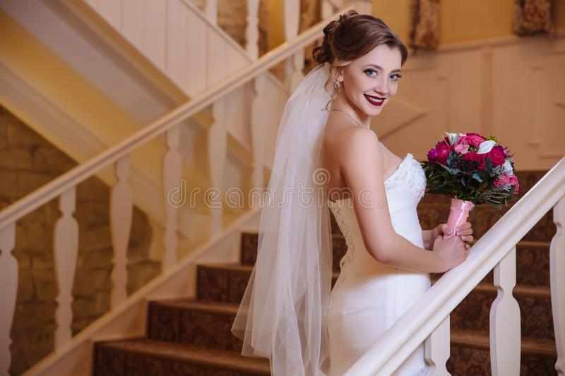 View from behind beautiful blond woman in veil and wedding dress holding bouquet, smiling and climbing up the stairs of stock photography
