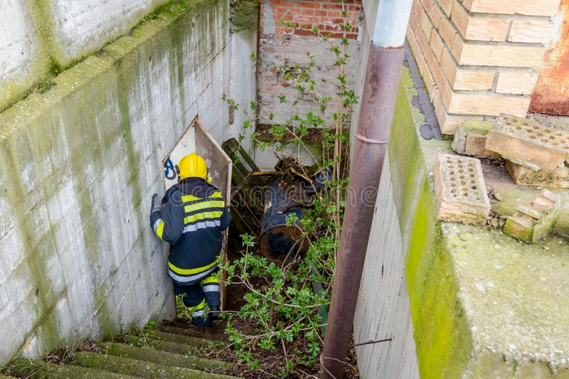 Firefighter is going down the stairs in industrial complex. View from behind on firefighter in uniform is going down the staircase royalty free stock image