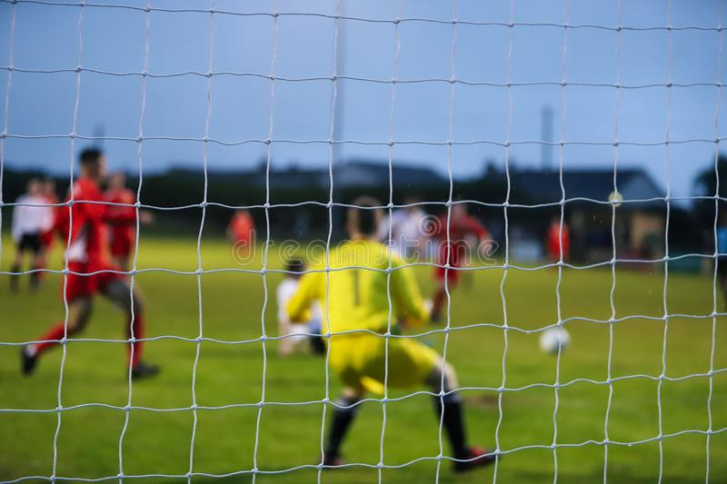 View from behind a footbal goal where the players are out of focus stock photo