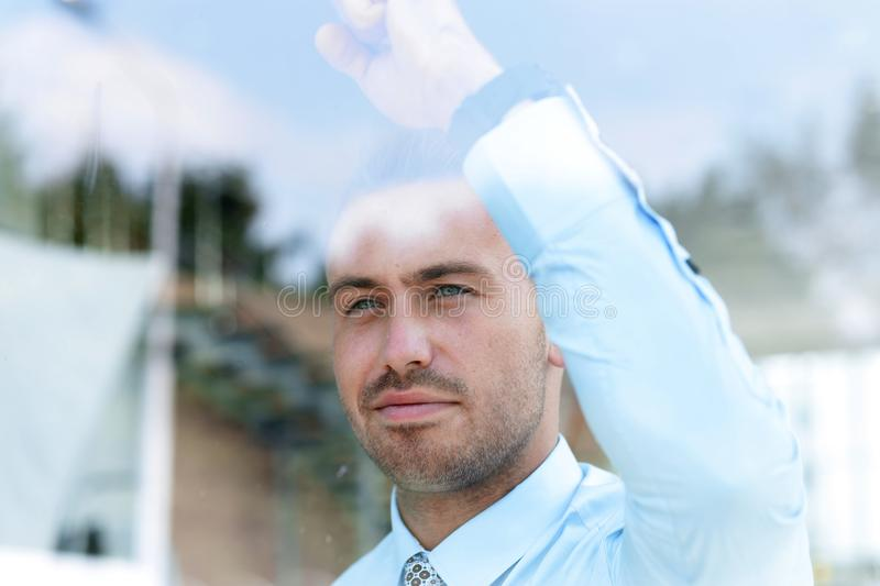 View from behind glass.businessman looking out the window of the office. View from behind glass.closeup .businessman looking out the window of the office royalty free stock photography
