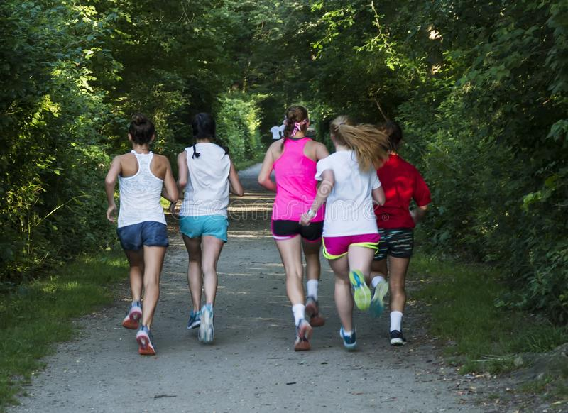 Group of girls running down a dirt path stock photo