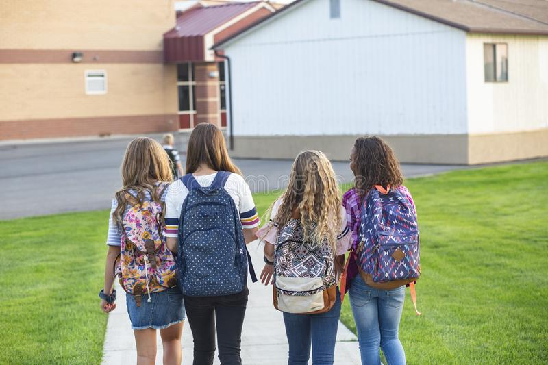 View from behind of a Group of school girls walking to school together stock photo