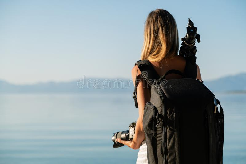 View from behind of professional female photographer with camera bag on her back. Standing by the sea holding camera in one hand and tripod leaning on her royalty free stock image