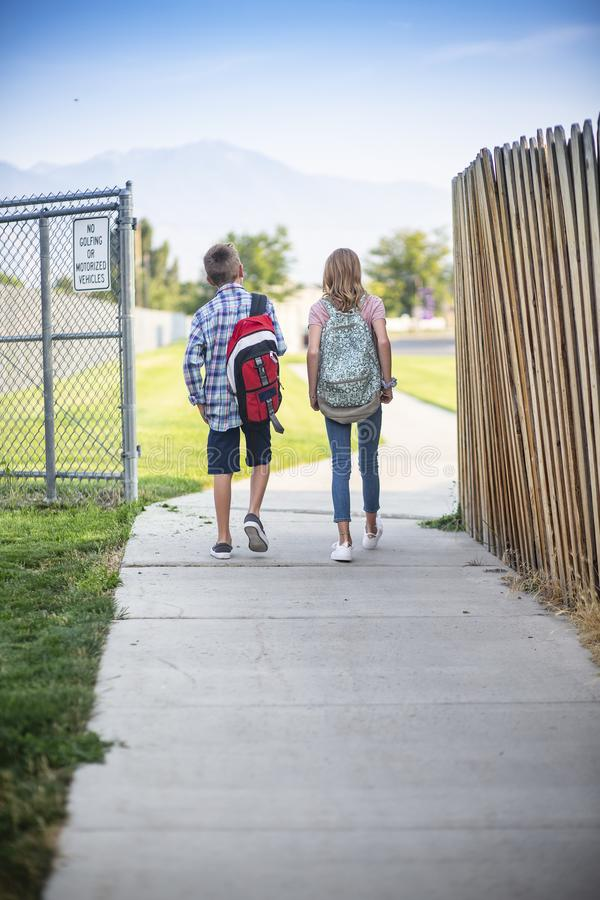 View from behind of two elementary school students walking to school together royalty free stock photo