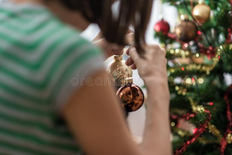 View from behind of a woman holding holiday baubles royalty free stock image