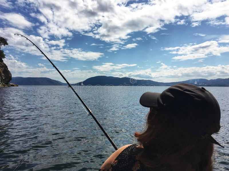 A view from behind of a young beautiful woman holding a fishing rod fishing in the ocean on a small boat in the gulf islands stock images