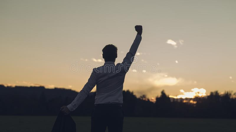 View from behind of a young businessman standing in a meadow stock images