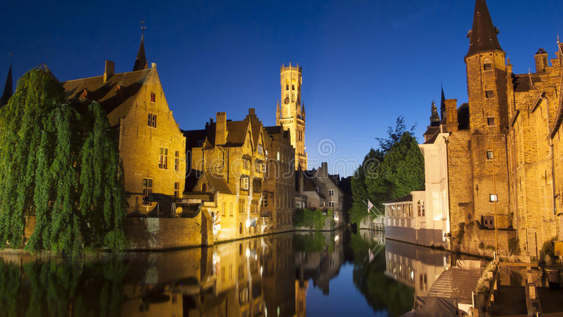 View of the Belfort and one of the canals of Bruges at night (Belgium). View of the Belfort and one of the canals of Bruges (Belgium) from the dock of the stock photo