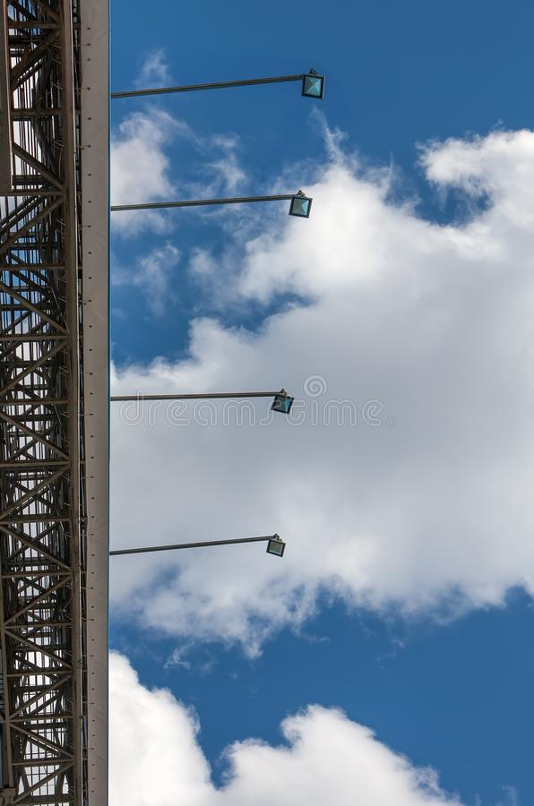 Beautiful view from below on bright blue sky and billboard backlight lamps. Sunny day. stock images