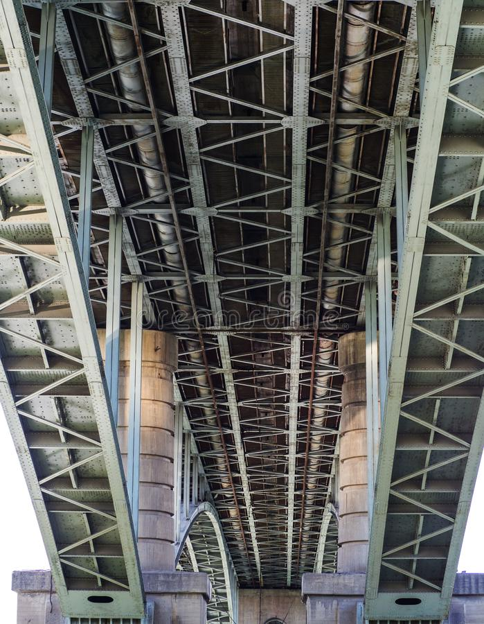A view from below on the design of the bridge. Concrete piles and iron slabs stock photography