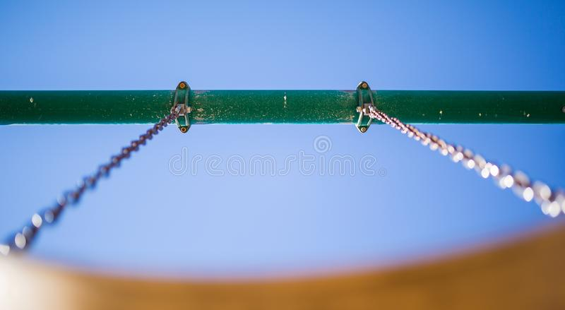 Playground swing support chains and bar. View from below and looking up at a playground swing`s support bar and swing chains stock photos