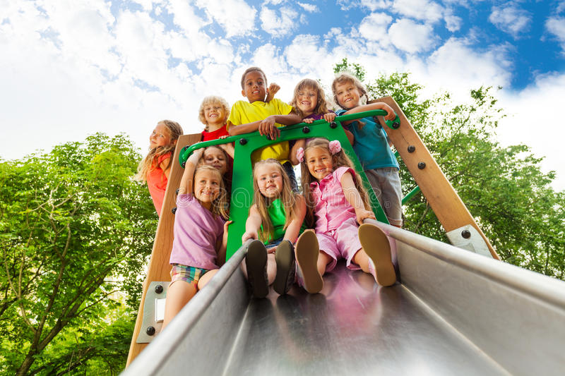 View from below of many kids on playground chute. Being happy together royalty free stock photography