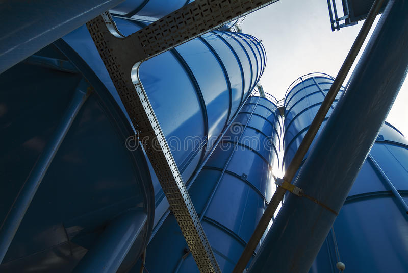 View from below of Tower Silos Bulk Storage. Bottom perspective of storage Tower Silos blue royalty free stock photos