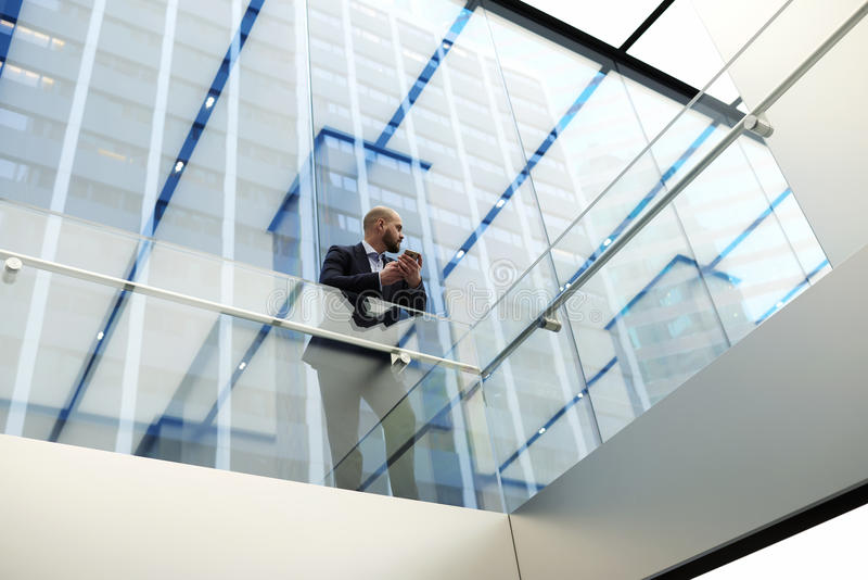 View from below of a young economist of a successful company is waiting for a call on mobile phone. Male CEO is standing in skyscraper office interior with stock photos