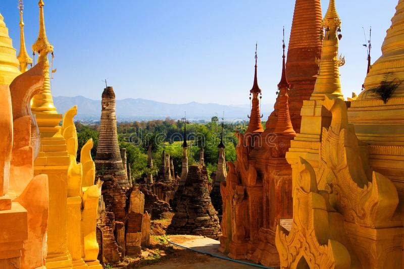 SHWE INDEIN PAGODA, MYANMAR - DECEMBER 23. 2015: View beyond old stone pagodas over green valley on mountain range. View beyond old stone pagodas over green royalty free stock photography