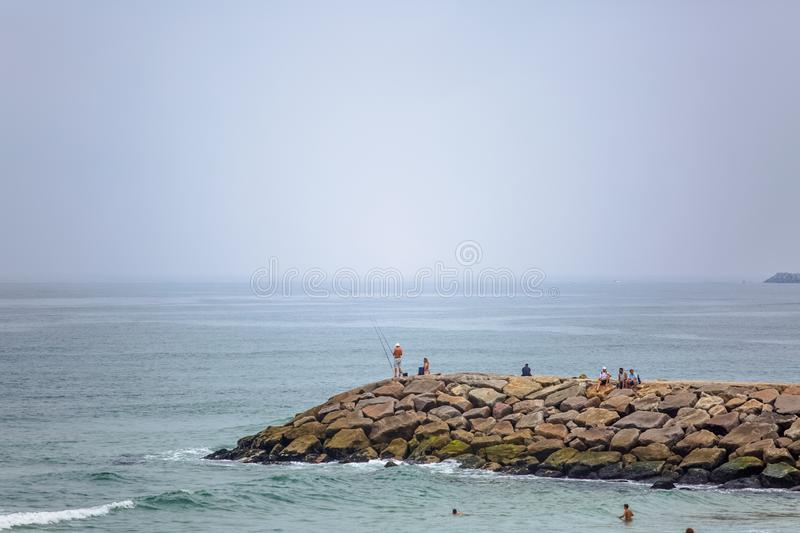 View of a big seawall on atlantic ocean and people enjoying the view and fishing stock images