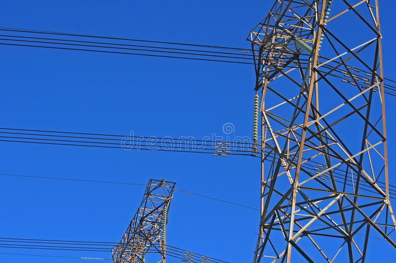 DETAIL OF ELECTRICAL PYLONS AGAINST DEEP BLUE SKY stock image