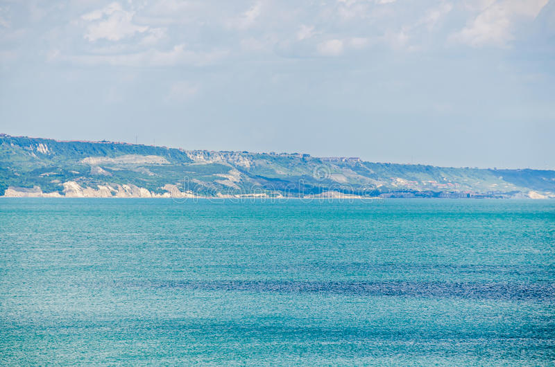 View of the Black Sea shore, green hills, blue clouds sky. City Balchik coast, blue clear sea water stock images