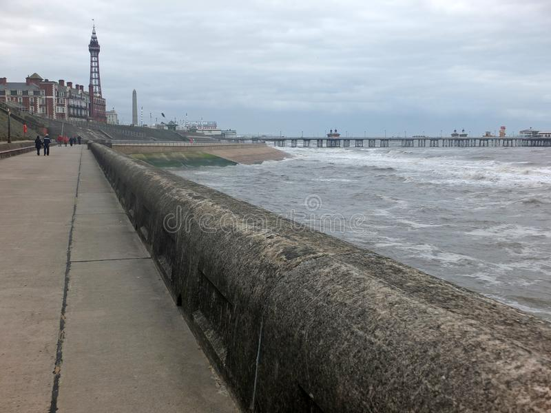 view of blackpool promenade in winter with stormy sea tower and central pier with unidentifiable people walking along the stock image