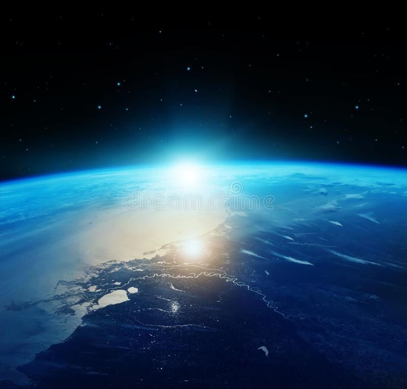 View of blue planet Earth with sun rising from space. royalty free stock photos