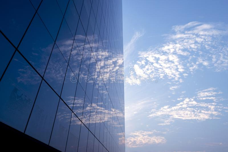 View of the blue sky and clouds reflect on glass window at modern business office building royalty free stock image