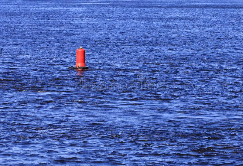 Red buoy bobs on the blue waves of a wide river stock images