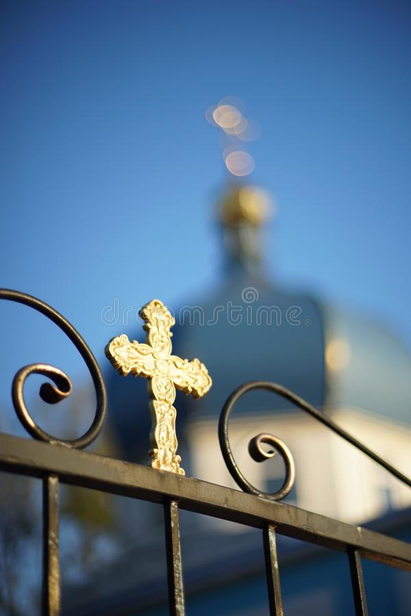 View of the blurred Orthodox Church through a fence with a cross stock photo