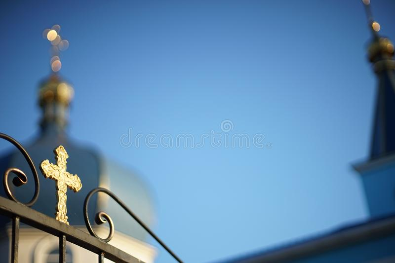 View of the blurred Orthodox Church through a fence with a golden cross stock photography