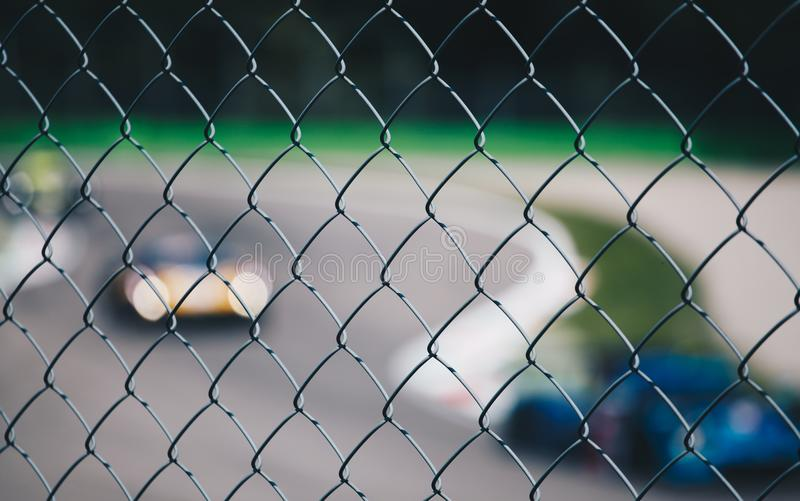 View of blurred racing car from a metal grid - sport background royalty free stock images