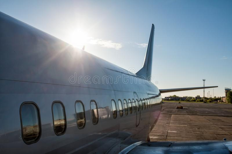 View from the boarding steps to the rear of the passenger plane in the rays of the rising sun stock image