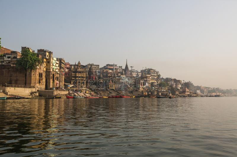 View from a boat glides through water on Ganges river along shore of Varanasi. India royalty free stock image