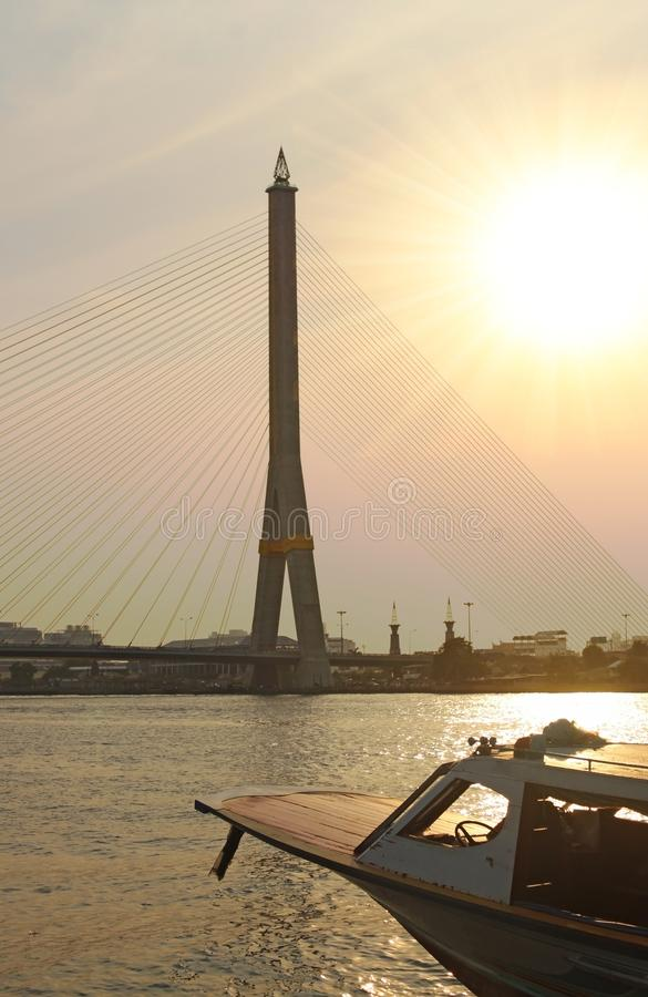 View of a boat in the river, the bridge tower and city on background under orange sky evening sunset, backlight photo. View of a boat in the river, bridge tower royalty free stock photo