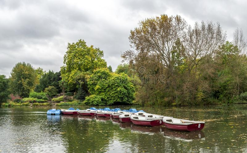 View of a boating lake with row and paddle boats parked, Battersea Park, London, United Kingdom. October 2017 royalty free stock image