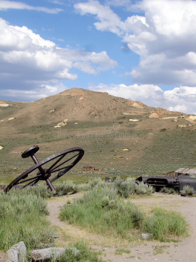 View from Bodie. Rusty wheel from ghost town Bodie with hill and clouds - Gold seeking - California state park - USA 2006 stock photos