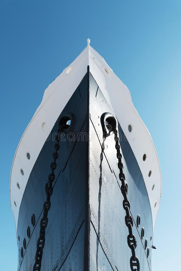 The bow of an old ship. A view of the bow of a moored ship, painted white and navy, against the blue sky royalty free stock images