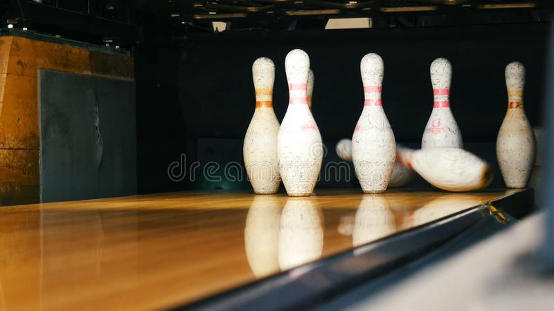 View of bowling pins standing in th end of bowling alley and bowling ball rolling on the wooden surface in a sport club. Media. Funny sport weekends in a stock photography