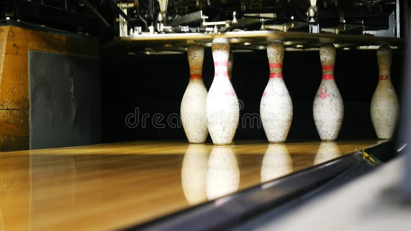 View of bowling pins standing in th end of bowling alley and bowling ball rolling on the wooden surface in a sport club. Media. Funny sport weekends in a stock images