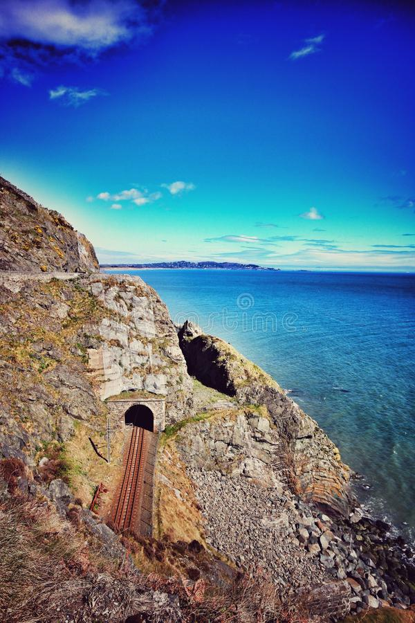 Bray Head cliffs in Ireland. View of the Bray Head cliffs with the railroad passing through the rock near Dublin in Ireland stock photos