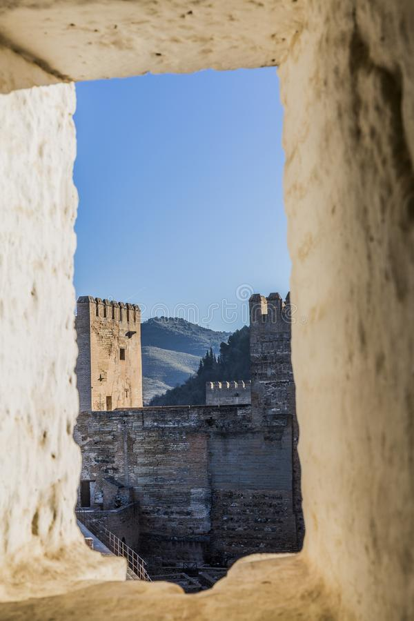 View of a brick wall and a tower in the Alhambra through a stone window. On a beautiful sunny day in Granada Spain royalty free stock photography