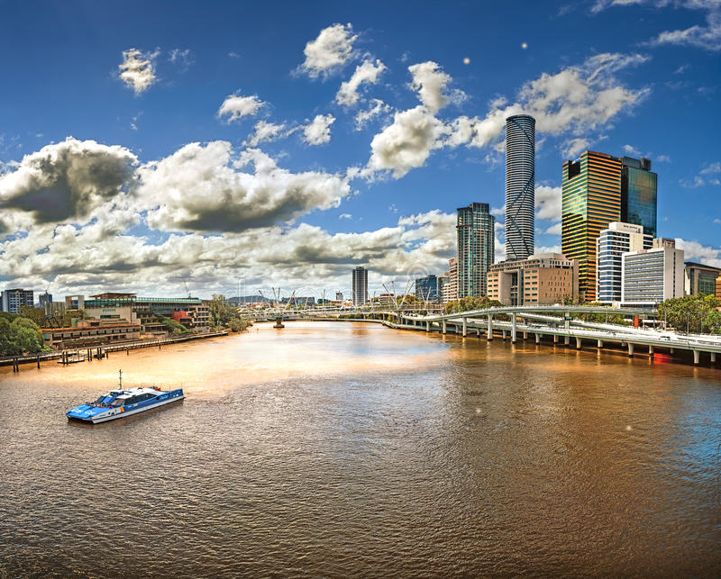 View from the Bridge over the River Brisbane (Australia, Brisbane) with views of the skyscrapers of the city. A boat in the foreground, with cloudy sky royalty free stock photography