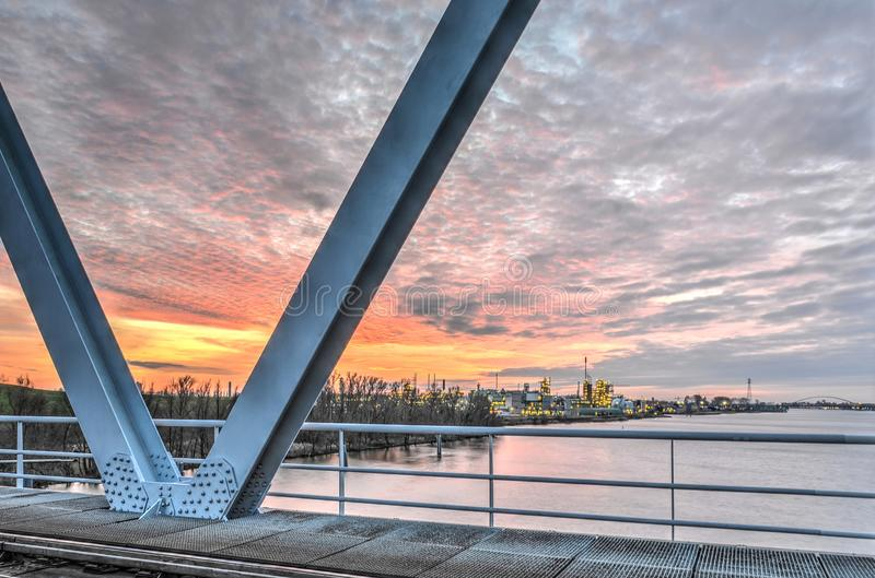 View from the bridge. Sliedrecht, The Netherlands, December 26, 2015: View from the railway bridge across the Beneden Merwede river towards the Chemours refinery royalty free stock photos