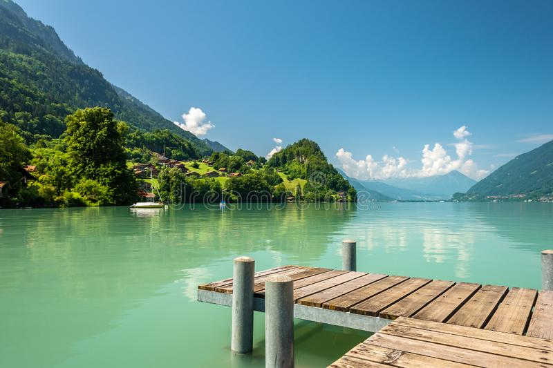 View of Brienz lake with clear turquoise water. Wooden pier. Traditional wooden houses on the shore of Brienz lake in royalty free stock photos