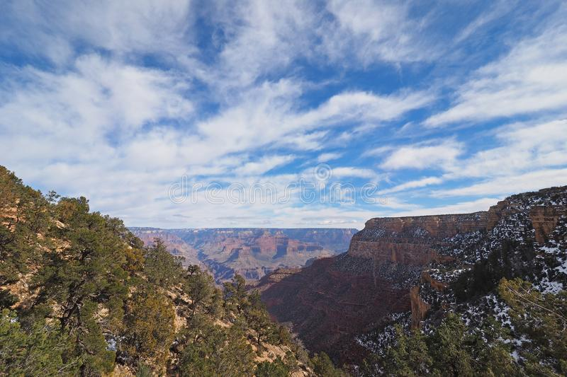 View from the Bright Angel Trail in the Grand Canyon in winter. Winter canyon view under a brilliant cloudscape from the Bright Angel Trail in Grand Canyon royalty free stock images