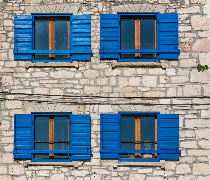 View of bright blue wooden windows and shutters on a mediterranean old stone house in Croatia stock photo