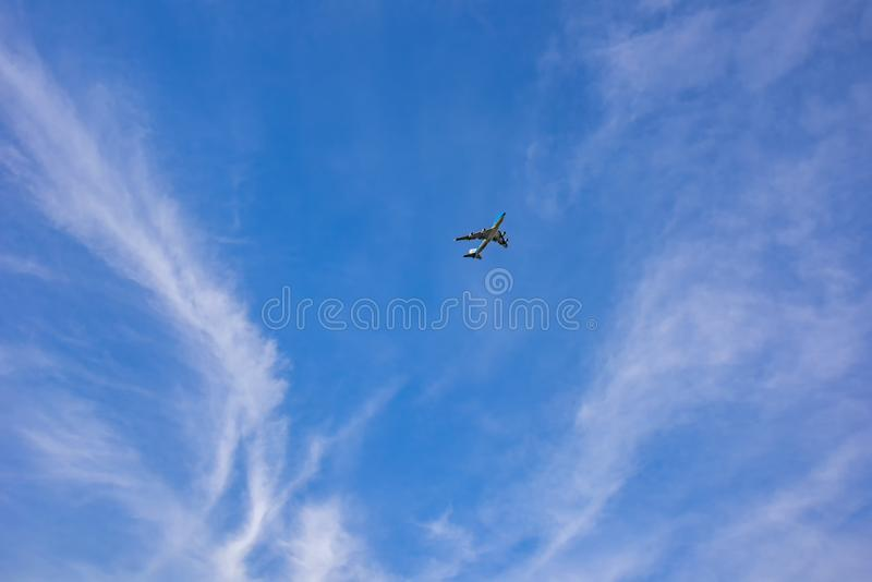 View of the bright blue sky, with white veil clouds, in which a plane with its nose in the sky is rising high between the clouds . 216/5000 view of the bright stock photos