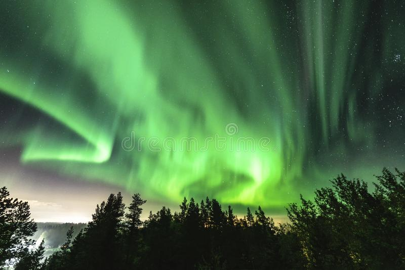 View of brilliant green Aurora shining over Swedish foggy forest landscape in mountains, light rays from a village and Northern stock photography