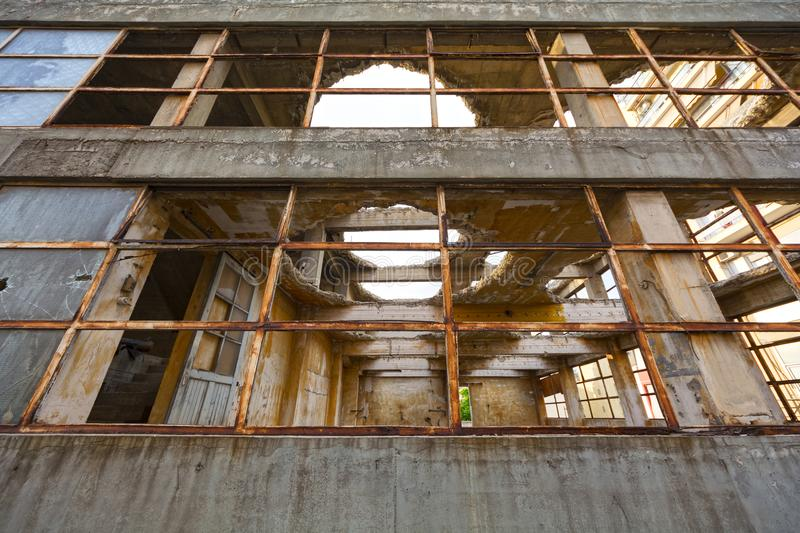 View through the broken windows of a demolished abandoned industrial building royalty free stock photo