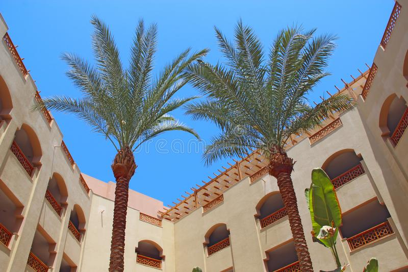 View of building of resort with palm trees. Egyptian resort. Tropical holidays. Hotel building with balconies. Modern arabic architecture. Two date palms royalty free stock photography
