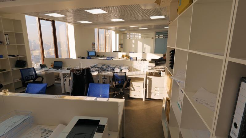 View of business office with one employee sitting at work alone. View of large open plan office with hard worker. Concept of office work stock photos
